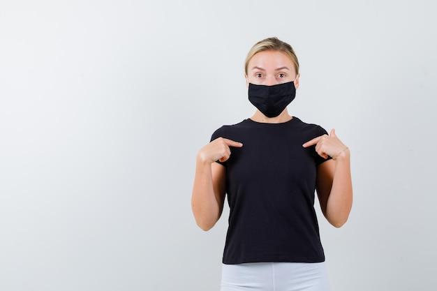 검은 티셔츠, 검은 마스크에 자신을 가리키고 고립 된 놀란 금발 아가씨