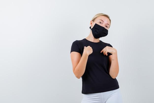 검은 티셔츠, 고립 된 검은 마스크에 자신을 가리키는 금발 아가씨