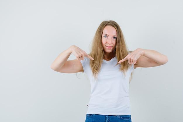 금발 아가씨 t- 셔츠, 청바지에 자신을 가리키는 자신감을 찾고,