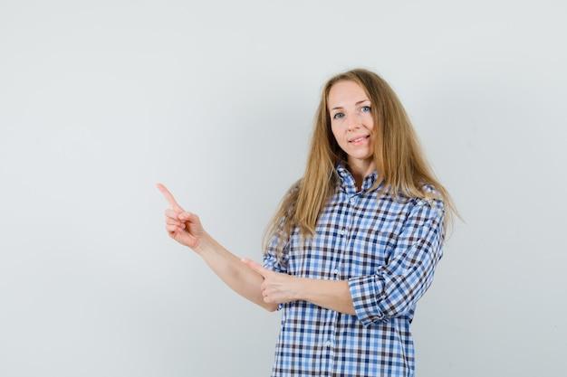 금발 아가씨 셔츠의 왼쪽 상단을 가리키고 자신감을 찾고.