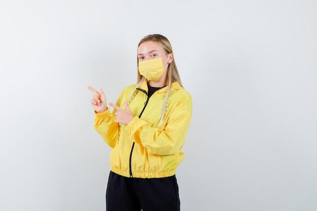 トラックスーツ、マスク、自信を持って、正面図で左上隅を指しているブロンドの女性。