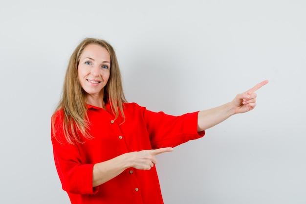 Блондинка в красной рубашке показывает на правый верхний угол и радостно смотрит