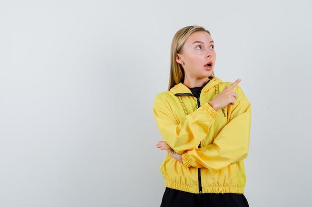 Блондинка, указывая на верхний правый угол в спортивном костюме и удивленно глядя, вид спереди.