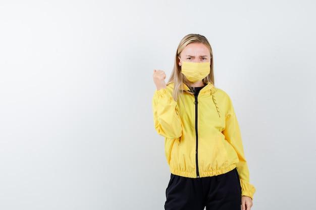トラックスーツ、マスク、気分を害した、正面図で親指で後ろを指しているブロンドの女性。