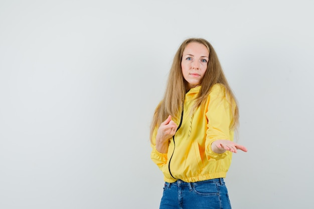 Signora bionda che indica la sua mano tesa in giacca, jeans e che sembra sicura.