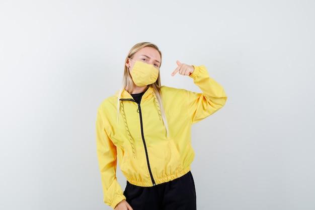 Signora bionda che indica a se stessa in tuta da ginnastica, maschera e guardando orgoglioso, vista frontale.