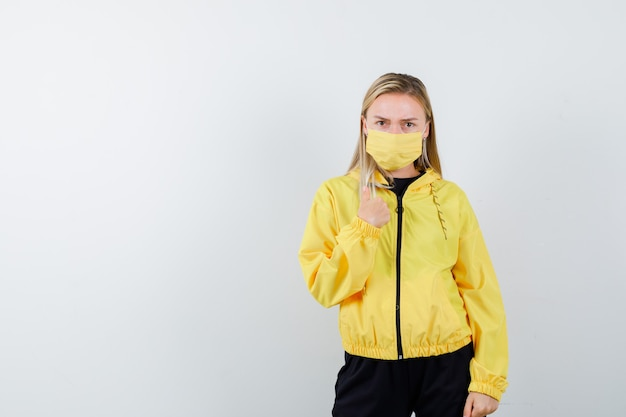 Blonde lady pointing at herself in tracksuit, mask and looking puzzled. front view.