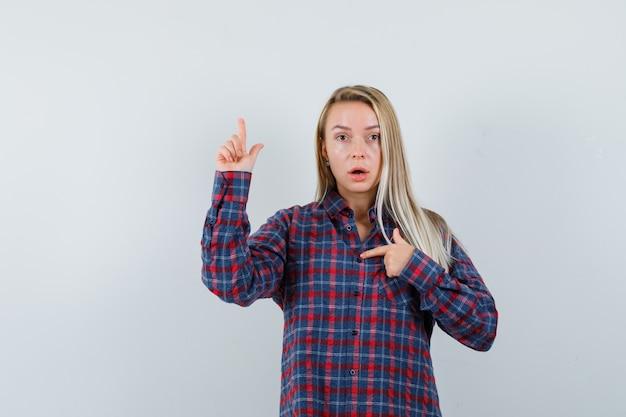 Signora bionda che indica se stessa e in alto in camicia casual e guardando meravigliato, vista frontale.