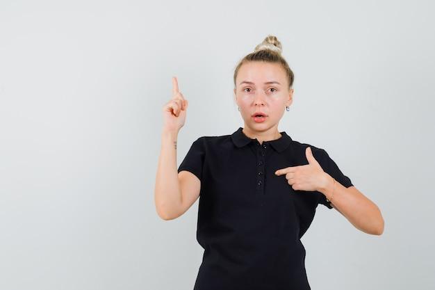 Signora bionda che indica a se stessa con il dito in alto in maglietta nera e guardando perplesso. vista frontale.