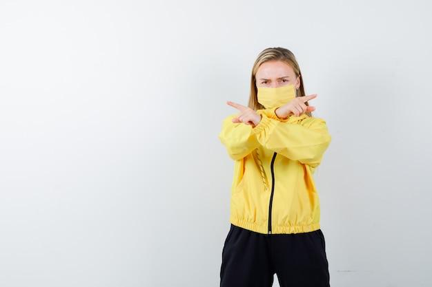Signora bionda che indica a destra ea sinistra in tuta da ginnastica, maschera e sguardo dispettoso. vista frontale.