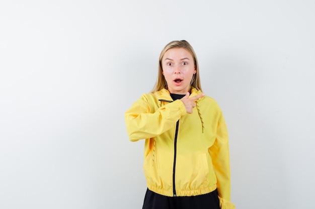 Signora bionda che indica a destra in tuta da ginnastica e sembra scioccata, vista frontale.