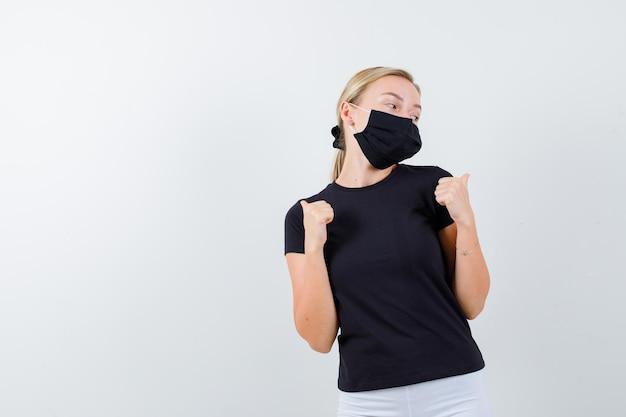 Signora bionda che punta i pollici indietro in maglietta nera, maschera nera e sembra pensierosa isolata