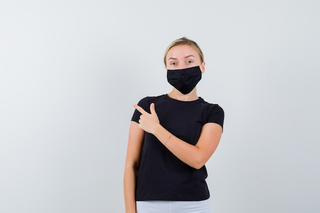 검은 티셔츠에 왼쪽을 가리키는 금발 아가씨, 고립 된 검은 마스크