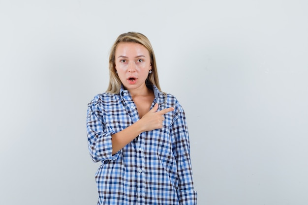 チェックシャツで右側を指して困惑している金髪の女性