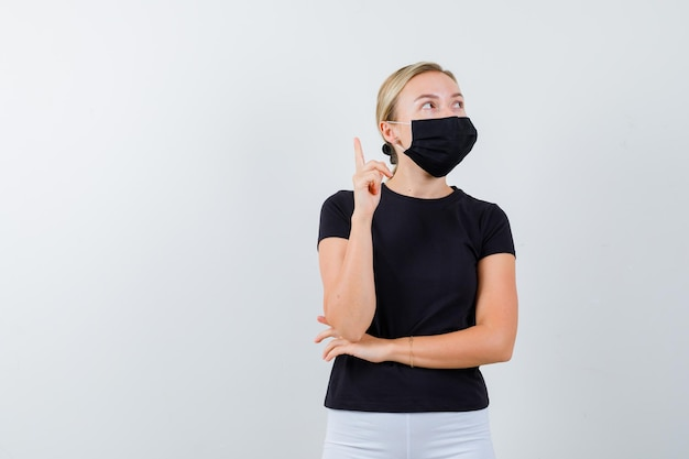 Blonde lady pointing up in black t-shirt, black mask and looking pensive
