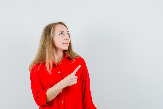 赤いシャツを着て、希望に満ちた金髪の女性、