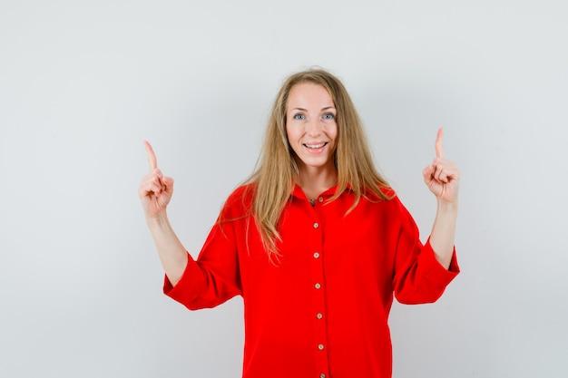 Signora bionda che indica in su in camicia rossa e che sembra felice.