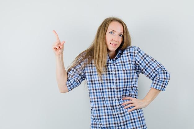Signora bionda che indica in su in camicia e che sembra gioviale.