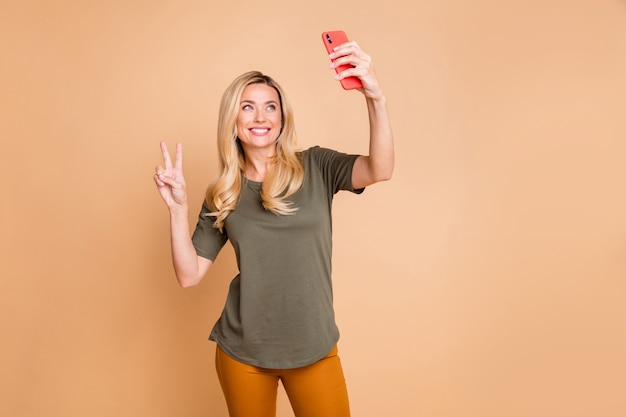 Blonde lady posing against the beige wall