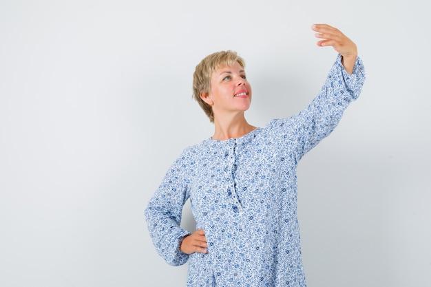 Signora bionda in posa come scattare foto selfie in camicetta fantasia e sembra felice. vista frontale.