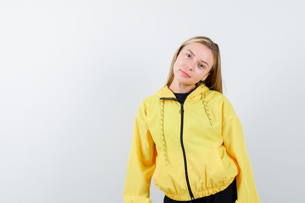 Blonde lady posing while bowing head on her shoulder in tracksuit and looking elegant , front view.
