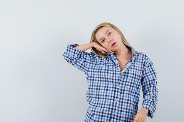 カジュアルなシャツに立って繊細に見えながらポーズをとる金髪の女性
