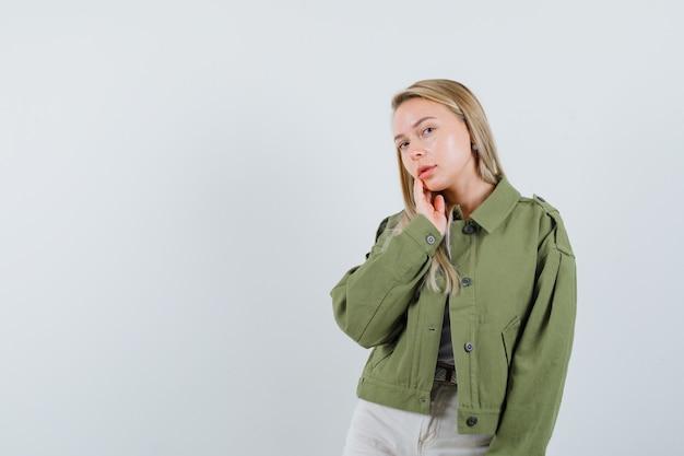 Блондинка позирует, стоя в куртке, штанах и выглядит нежно, вид спереди.