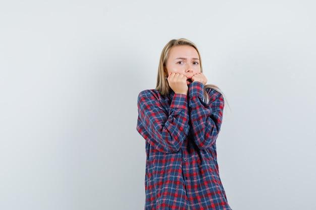 カジュアルなシャツを着て頬に拳を押し付け、怖がっている金髪の女性。正面図。