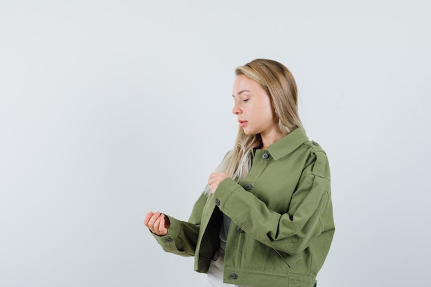 Blonde lady pretending to hold something in jacket, pants and looking focused , front view.