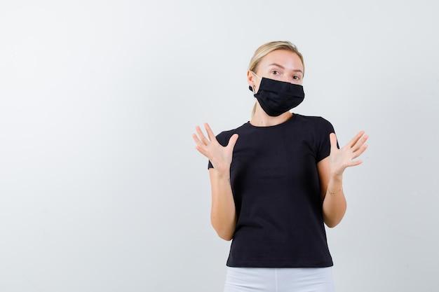 黒のtシャツで身を守るふりをしている金髪の女性