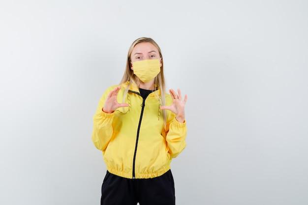 トラックスーツ、マスク、自信を持って、正面図で何かを保持または表示するふりをしているブロンドの女性。