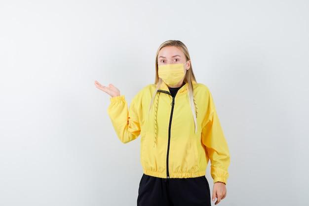 トラックスーツ、マスクで何かを見せているふりをして、当惑したように見えるブロンドの女性、正面図。