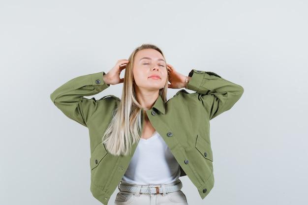 ジャケット、パンツにヘッドホンを使用するふりをして喜んでいる金髪の女性。正面図。