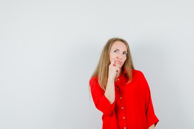 Signora bionda appoggiando il mento sul pugno in camicia rossa e guardando esitante,