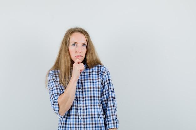 Signora bionda appoggiando il mento a portata di mano in camicia e guardando esitante.