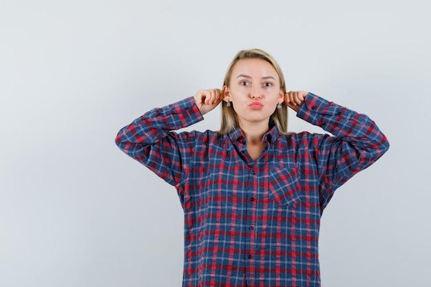 Блондинка тянет за уши, надувает губы в повседневной рубашке и выглядит забавно, вид спереди.