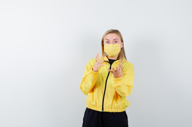 Tracksuit, 마스크 및 흥분 찾고 의아해 제스처에 손을 올리는 금발 아가씨. 전면보기.