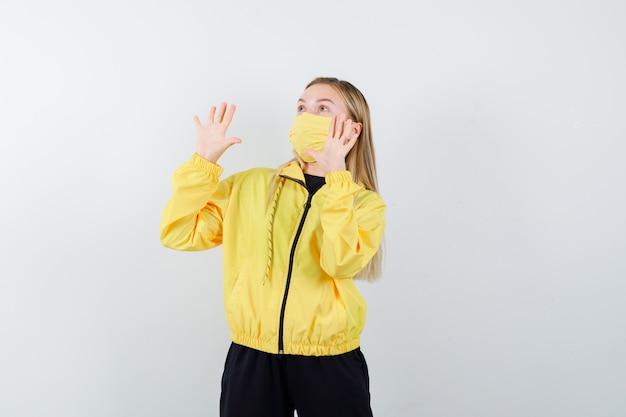 トラックスーツ、マスク、怖い顔で降伏ジェスチャーで手を上げる金髪の女性。正面図。