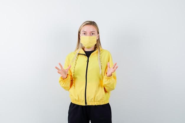 トラックスーツ、マスクで手を上げて困惑している金髪の女性。正面図。