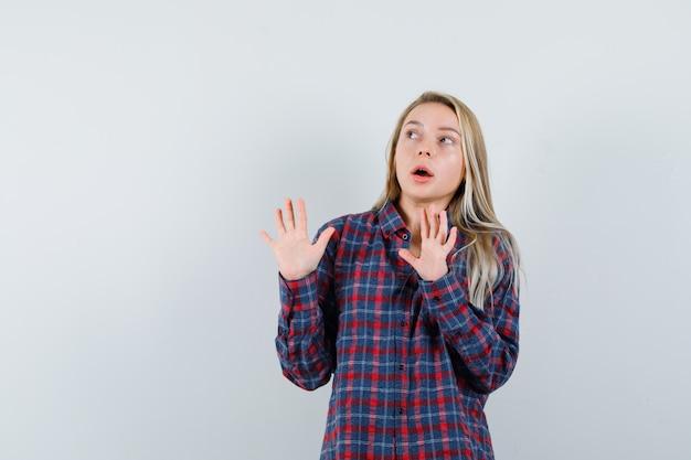 カジュアルなシャツを着て身を守るために手を上げて怖がっている金髪の女性、正面図。