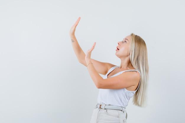一重項、ズボンで身を守るために手を上げて、問題を抱えているように見えるブロンドの女性