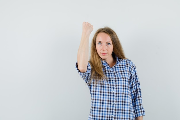 Blonde lady raising her clenched fist in shirt and looking strong.