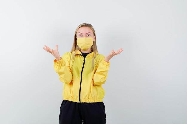 トラックスーツ、マスクで広げられた手のひらを上げて、当惑したように見えるブロンドの女性、正面図。