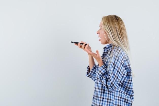 Signora bionda che registra un messaggio vocale in camicia a quadri e sembra emotiva. .