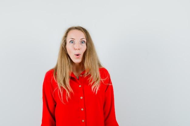 Signora bionda in camicia rossa che guarda l'obbiettivo e guardando stupito,