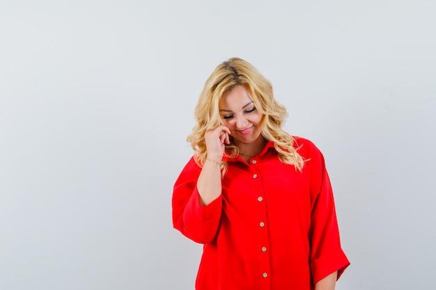 Signora bionda in camicia rossa sorridente e alla ricerca di spazio timido per il testo