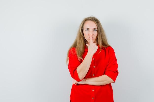 Signora bionda in camicia rossa che tocca il naso con il dito e sembra adorabile,
