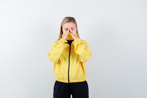 Blonde lady rubbing eyes and nose in tracksuit, mask and looking fatigued. front view.