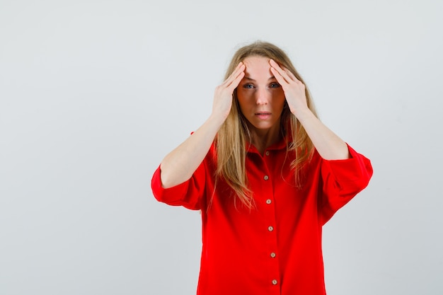 Blonde lady rubbing forehead in red shirt and looking perplexed ,