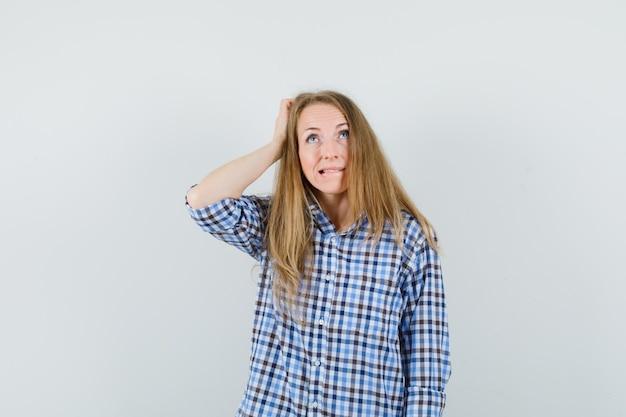 금발 아가씨가 머리를 긁고, 셔츠에 입술을 물고 혼란스러워 보입니다.